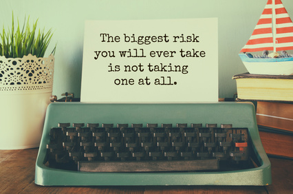 """vintage typewriter and paper with the printed text """"The biggest risk you will eve take, is not taking one at all"""""""